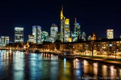 Die erleuchtete Frankfurter Skyline von einer Brücke über dem Main aus gesehen